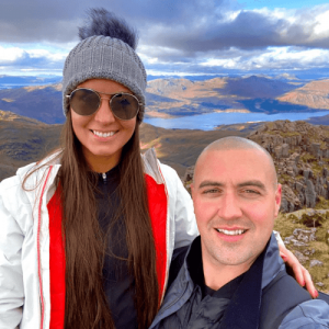 client with his wife on a mountain showing off his scalp micropigmentation