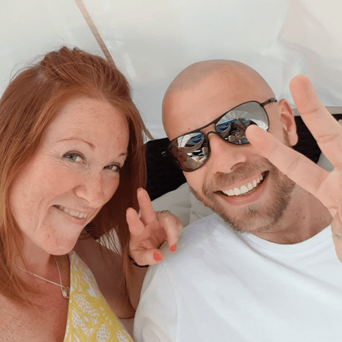 Man showing off his scalp micropigmentation in a tent with his wife